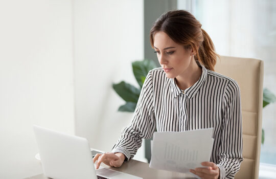Woman sitting at desk working on laptop with sheets of paper in hand