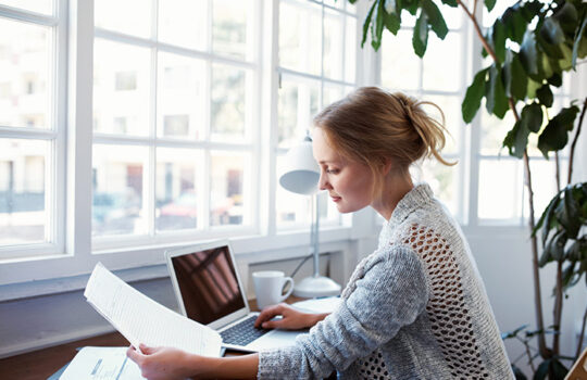 Woman working at laptop sitting at her desk in front of window