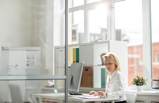Woman working at a computer at her desk in an office